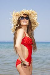 Woman with straw hat on the beach