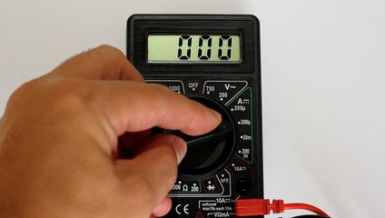 Man measures digital multimeter