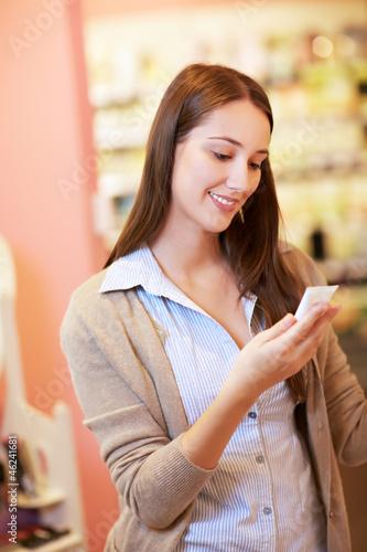 Frau in Drogerie schaut auf Produkt