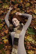 Beautiful young woman laying in fallen leaves.