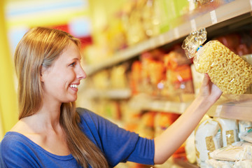Frau kauft Hörnchennudeln im Supermarkt