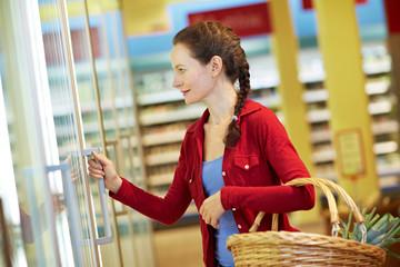 Frau öffnet Kühlregal im Supermarkt