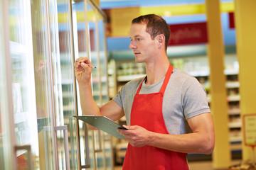 Mitarbeiter kontrolliert Warenbestand im Supermarkt