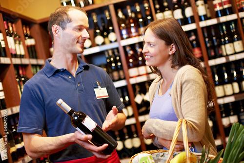 Sommelier berät Frau beim Weinkauf