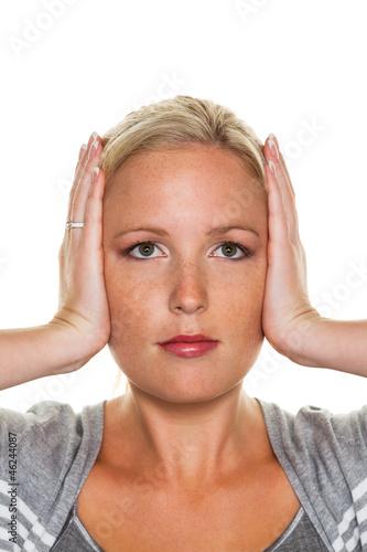 Frau hält sich die Ohren zu