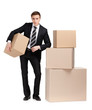 Manager in suit stands near pile of boxes, isolated on white
