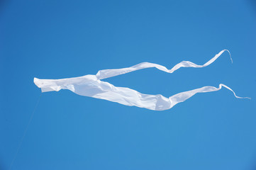 White kite flag in the blue sky.