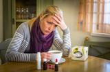 Frau mit Tee und Medikamenten