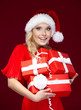 Woman in Christmas cap holds  gifts wrapped with red paper