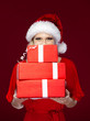 Woman in Christmas cap hands gifts wrapped with red paper