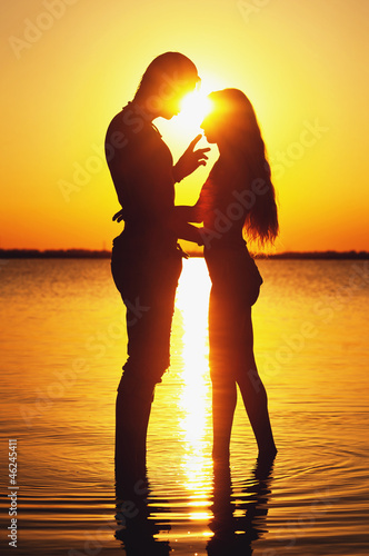 Couple silhouette at the beach. Sunset light.