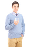 Casual guy holding a glass of water and posing