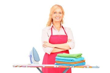 Woman standing next to an ironing board