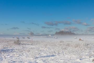 snowy hay bales in fog