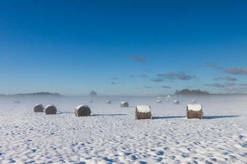 snowy hay bales with fog