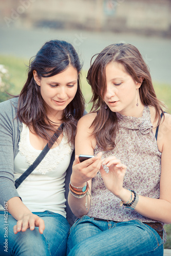 Two shopping girls in park with a mobile phone