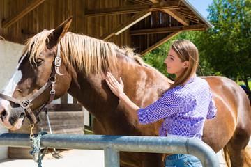 Junge Frau im Stall mit Pferd