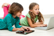Two kids on floor with laptop and tablet.