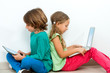 Two kids socializing with laptop and tablet.