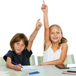 Two young students raising hands at desk.