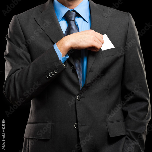 Young business man puts a business card in the poket