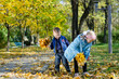 Children having fun collecting autumn leaves
