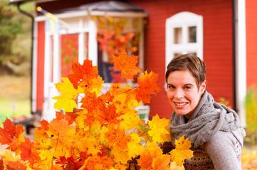 Attraktive Frau mit Strauß aus Herbstlaub
