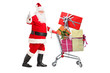 Santa Claus pushing a shopping cart full of gifts and giving a t