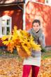 Junge Frau mit Korb voller Herbstlaub