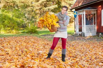 Attraktive Frau vor rotem Holzhaus in Schweden im Herbst