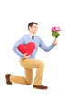 Smiling male kneeling with bouquet of flowers and red  heart