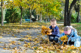 Youngsters collecting autumn leaves poster
