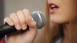 Close-up of singer touching microphone  singing