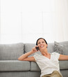 Happy young woman sitting on floor and speaking cell phone