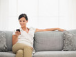 Happy young woman sitting on sofa and reading sms on mobile phon