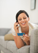 Happy woman on sofa holding credit card and speaking mobile