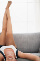 Closeup on young woman laying o sofa upside down