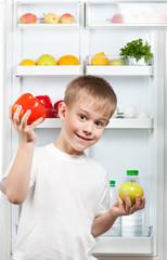 happy boy near the open refrigerator