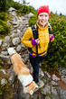 Woman hiking in mountains and walking akita dog