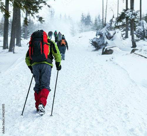 People hiking on snow trail in winter