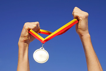 Hands holding gold medal on sky background