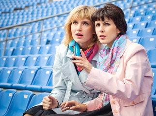 two excited  women fans watching  competition or concert in stad