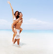 Romantic young couple at the beach in playful mood
