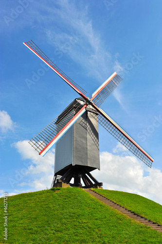 Dutch windmill on green hill with blue sky ( Holland )
