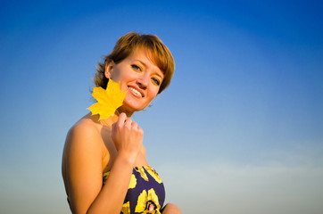 young woman on a background of blue sky with yellow leaves