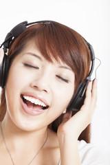 asian woman listening and enjoying music in headphones