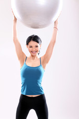 Cute and young fitness girl with abs ball