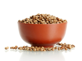 Heap coriander seeds in ceramical bowl isolated on white