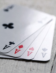 4 aces on a white wooden surface