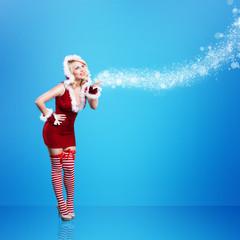 Weihnachtsfrau im roten Minikleid vor blauem Hintergrund